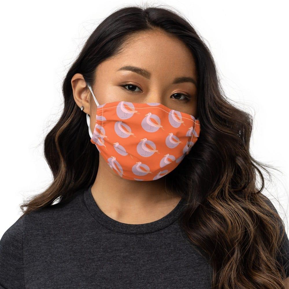 Orange face mask with bird print in orange and mauve.