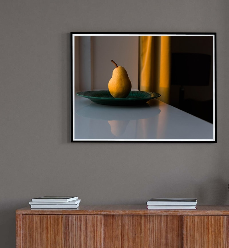Fine art print of pear and golden curtain on display above wooden sideboard.