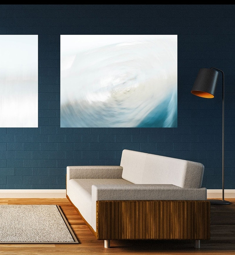 White painted canvas artwork with blue streaks on a dark blue wall.